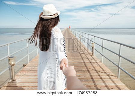 Follow me. Beautiful young woman in hat holding hand and leading her friend on pier