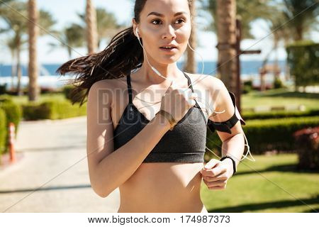 Portrait of lovely young sportswoman running and listening to music with earphones in summer