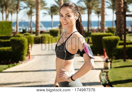 Happy young woman athlete with armband listening to music from cell phone on summer resort