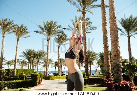 Fitness woman with armband standing and stretching outdoors in summer
