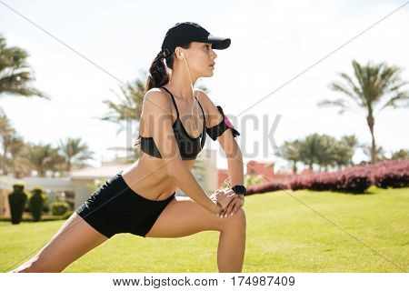 Beautiful young woman athlete in cap listening to music and doing stretching exercises on lawn