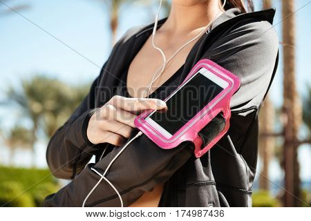 Closeup of woman athlete using blank screen cell phone in armband on summer resort