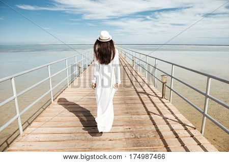 Back view of attractive young woman with long dark hair in white clothes and hat walking on pier