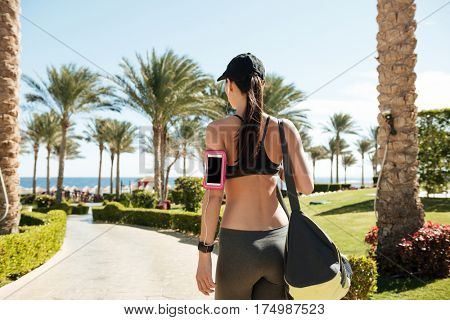Back view of fitness woman with bag and blank screen cell phone in armband in summer resort