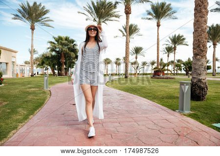Happy attractive young woman in hat and sunglasses walking on summer resort