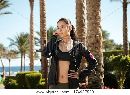 Attractive young sportswoman listening to music with earphones on summer resort