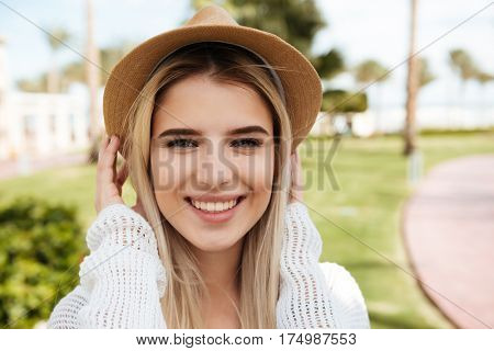 Portrait of cheerful beautiful young woman in hat standing outdoors