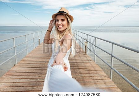 Follow me. Cheerful young woman in hat holding hand and walking with her friend on pier