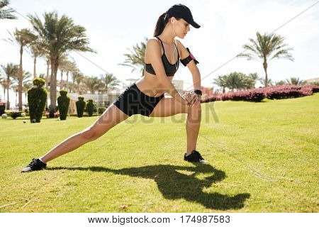 Concentrated young fitness woman in cap stretching and exercising in summer on lawn