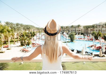 Back view of beautiful young woman in hat standing on summer resort