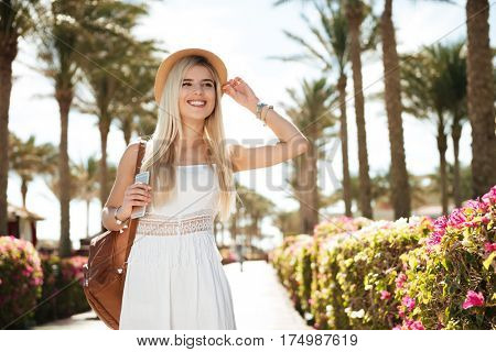 Happy beautiful young woman with bag and mobile phone walking on summer resort