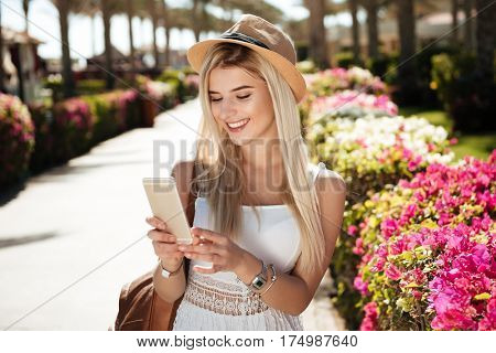 Happy pretty young woman in hat walking and using smartphone on summer resort
