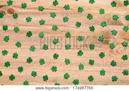 St Patrick's Day. St Patricks Day background - green quatrefoils on the natural wooden surface. St Patrick's Day background with St Patrick's Day symbols. St Patrick's Day concept