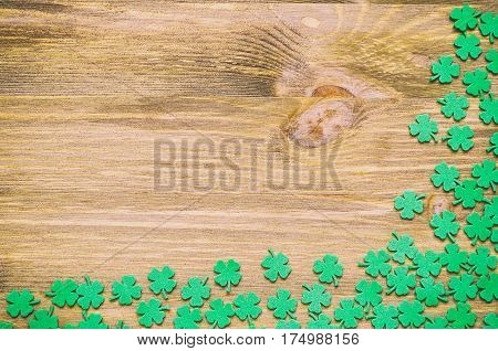 St Patricks Day background - green quatrefoils on the wooden surface. St Patrick's Day background with St Patrick's Day symbols. St Patrick's Day concept. St Patrick's Day background