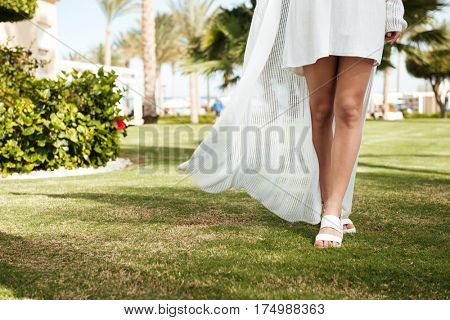 Closeup of woman in white clothes walking on lawn on summer resort