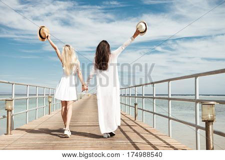 Back view of two attractive young women with raised hands holding hats and walking on pier