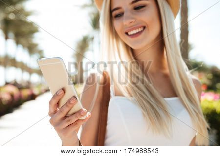 Happy attractive young woman using mobile phone in summer resort