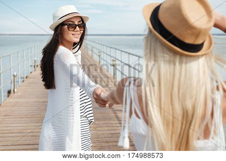 Two happy young women in hats holding hands and walking on pier