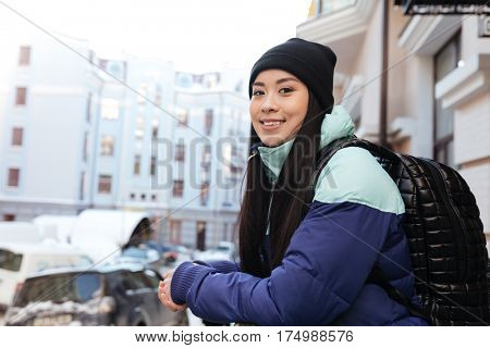 Side view of Asian woman in warm clothes and with backpack which posing on the street and looking at camera