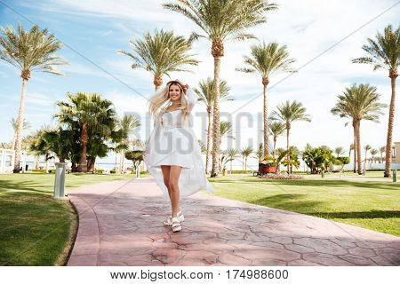 Happy beautiful young woman in white dress and hat standing and whirling on summer resort