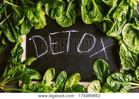 The inscription on the detox board and spinach around. Concept detox