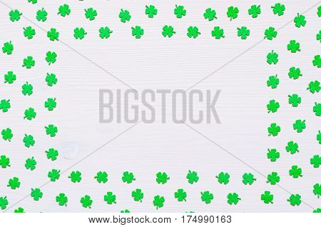 St Patrick's Day. St Patrick's Day background - green quatrefoils on the white wooden surface with free space for text. St Patrick's Day concept with St Patrick's Day symbols. St Patrick's Day festive background