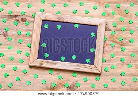 St Patrick's Day background - wooden frame with free space for text and green quatrefoils on the wooden surface. St Patrick's Day background, St Patrick's Day concept. St Patrick's Day background with clovers