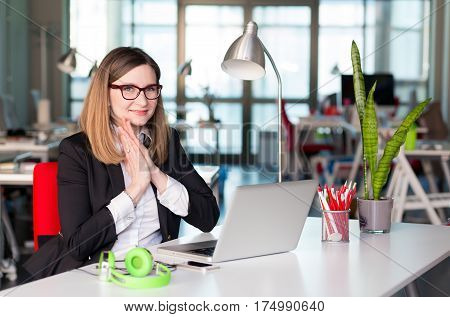 Beautiful Business Lady in official clothing black Jacket and white Shirt sitting at grey Table with Computer Flower and other Business Lifestyle Items smiling Face satisfied with good Job well done .