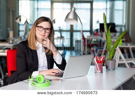 Beautiful Business Lady in official clothing black Jacket and white Shirt sitting at grey Table working on Computer in contemporary digital corporate Office with large Window on Background.