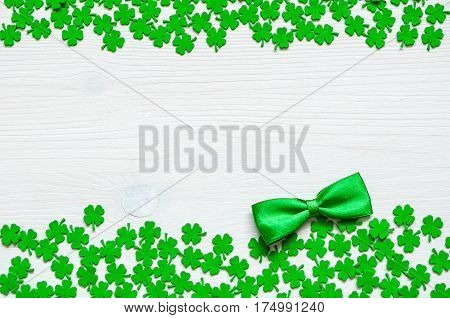 St Patrick's Day concept. St Patrick's Day background - green quatrefoils and bow tie on the wooden background with free space for text. St Patrick's Day background with St Patrick's Day symbols. St Patrick's Day background