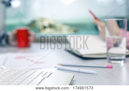 Office Life Concept - Computer Glass of Water and Stationery Pen color Pencil paper Workbook Coffee Mug on grey Table focus on rear end of Keyboard