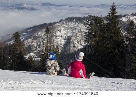 Two little girls skiers sitting in the snow in the mountains and consider the nature of the