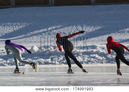 Speed skating competition on ice rink at winter sunny day - children's sport concept, telephoto