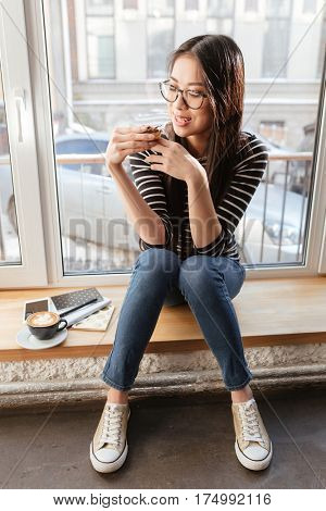 Vertical image of Asian woman in eyeglasses which drinking coffee on windowsill in cafeteria