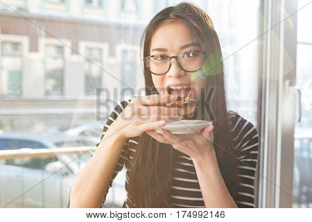 Asian woman in eyeglasses which eating cake and sitting on windowsill in cafeteria and looking at camera