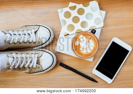 Top view of wooden board with phone, cofee, pen, gumshoes and notebook