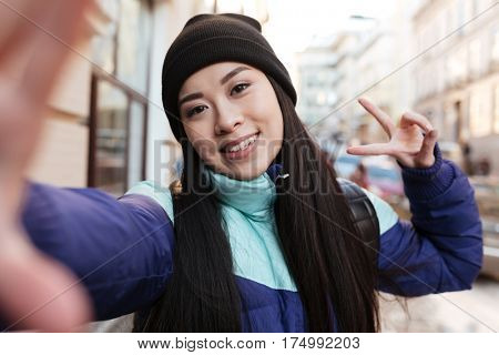 Asian woman in warm clothes which making selfie on the street