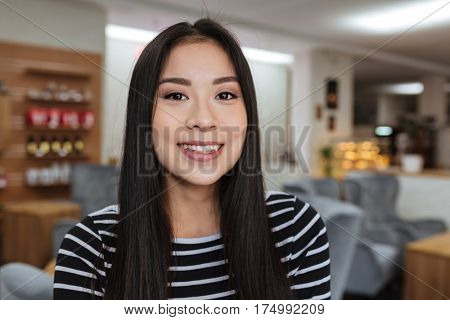 Close up portrait of Asian woman in sweater which posing in cafeteria and looking at camera