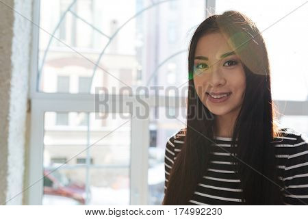 Smiling Asian woman in sweater which posing near the window in cafeteria and looking at camera