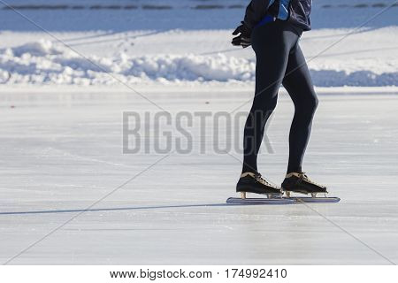 Man's legs on skates ice ring - winter sport at sunny day, telephoto close up