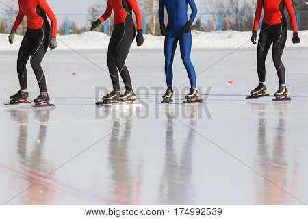 Speed skating competition on ice rink at winter sunny day - sportsmen ready for start, telephoto
