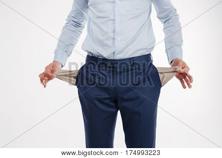 Cropped image of man in business clothes which showing empty pockets. Isolated white background