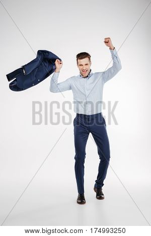 Vertical image of Happy man in business clothes which rejoices in studio. Isolated white background