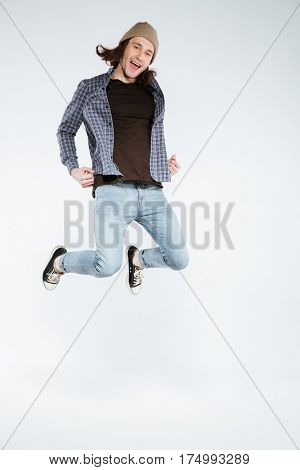 Vertical image of hipster which jumping in studio with open mouth and looking at camera. Isolated gray background