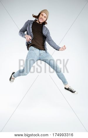 Vertical image of Smiling hipster which jumping and playing on imaginary guitar. Isolated gray background