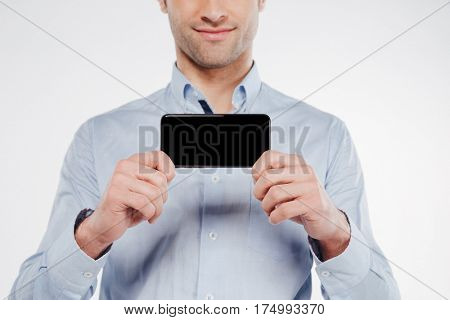 Cropped image of man in shirt which showing blank smartphone screen. Isolated white background