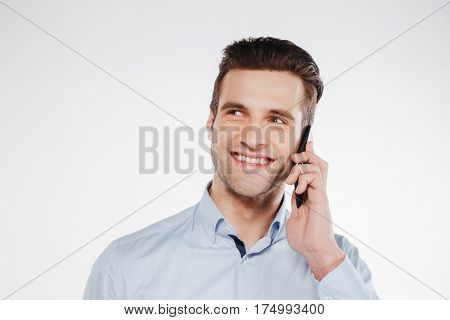 Close up portrait of Man in shirt which talking on the phone in studio. Isolated white background