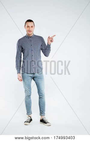 Vertical image of man in shirt and jeans which posing in studio and pointing away. Full length portrait. Isolated gray background