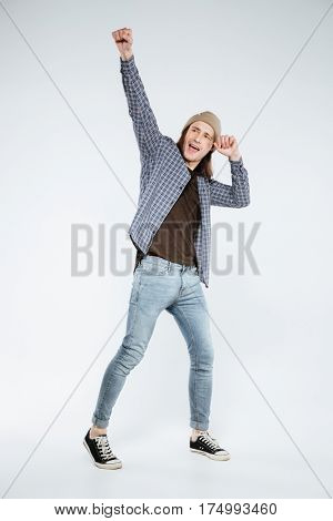 Vertical image of happy hipster which posing in studio and looking away. Isolated gray background