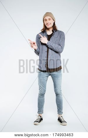Vertical image of hipster which pointing away and looking at camera. Isolated gray background